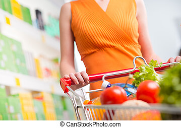 Woman at supermarket with trolley - Woman shopping at...