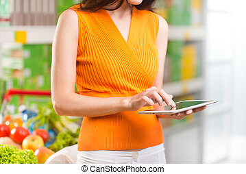 Woman using tablet at store - Young woman using a digital...