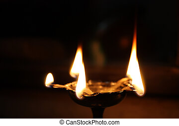 Holy Hindu Lamp - A traditional holy oil-lamp lit in a Hindu...