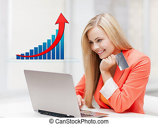 smiling woman with laptop computer and credit card - online...