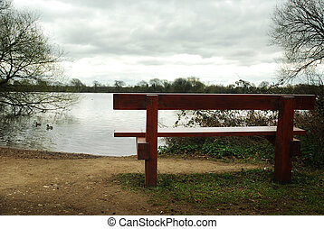 Bench in front of a murky lake