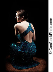 Glamourous woman facing to the side in sparkly dress
