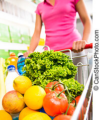 Shopping cart filled with vegetables and fruit - Woman at...