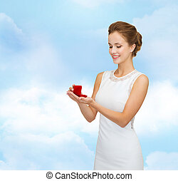 smiling woman holding red gift box with ring - wedding,...