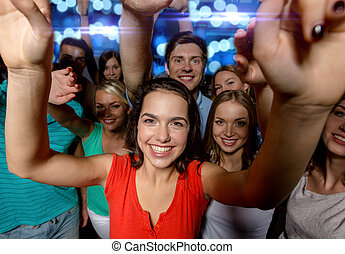 smiling women dancing in club - party, holidays,...