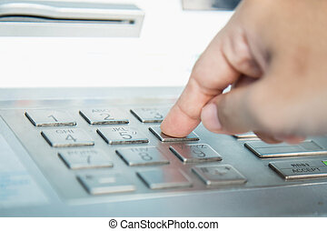Close up of hand entering PINpass code on ATMbank machine...