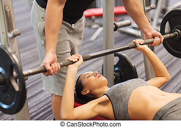 man and woman with barbell flexing muscles in gym - sport,...