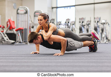smiling couple doing push-ups in the gym - fitness, sport,...
