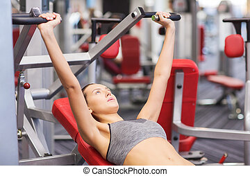 young woman exercising on gym machine