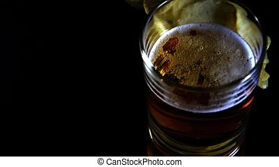 Beer and chips on black background
