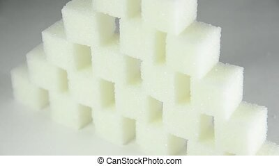 Pyramid of white sugar cubes rotating