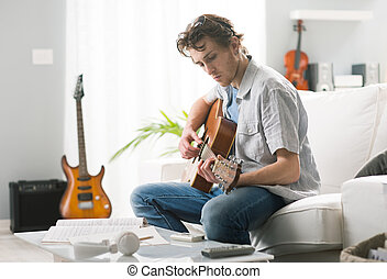Songwriter composing a song - Young man playing guitar and...