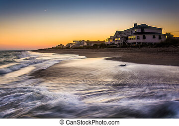 Waves in the Atlantic Ocean and beachfront homes at sunset,...