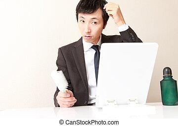 losing hair - Japanese businessman wearing suit worries...