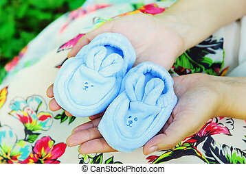 Pregnant woman with a belly holding baby shoes.