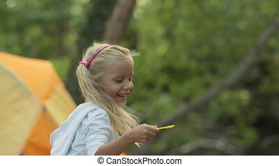 Little girl jumping with soap bubbles in the forest