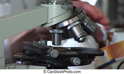 working in lab with microscope - Researchers working in lab...