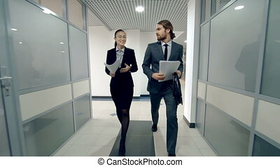 Career Path - Workmates strolling along the office corridor...