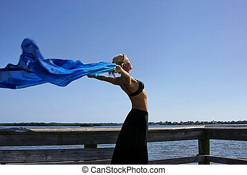 woman stretching in the sun - a beautiful fit woman is...
