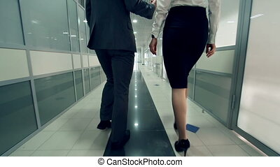 Charming Colleagues - Camera following man and woman in...