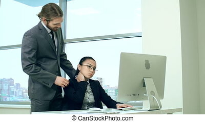 Workplace Massage - Businessman doing massage to his female...