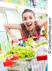 Full shopping cart at supermarket - Woman gasping and...