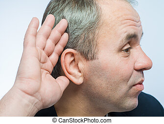 Businessman holds his hand near his ear and listening...