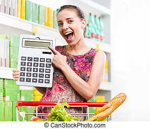 Budget friendly shopping at supermarket - Young woman...