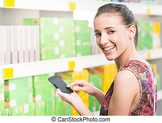 Woman with mobile at supermarket - Smiling young woman at...