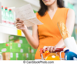 Woman at supermarket with shopping list - Young woman...