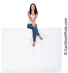 Sleeping - Beautiful young woman is sitting on mattress,...