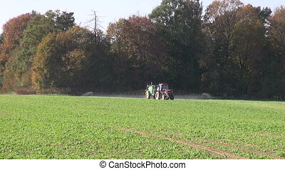 tractor spraying farm field - tractor spraying fertilizers...