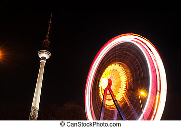 ferris wheel and television tower in berlin by night