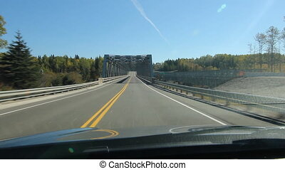 Driving across a long truss bridge.