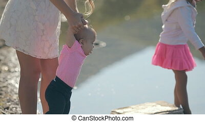 Feminine young mother stands with his charming daughter near lake