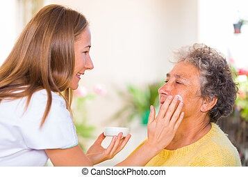 Elderly home care - Caregiver rubs the face cream on the...