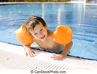 little cute boy in swimming pool wearing handcarves - little...