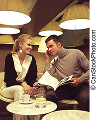 couple with cell phones - couple sitting in the cafe, both...