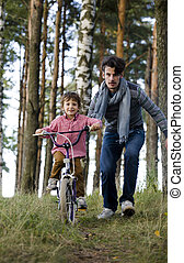 father learning his son to ride on bicycle outside in park,...