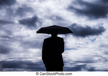 businessman holind an umbrella and stormy clouds