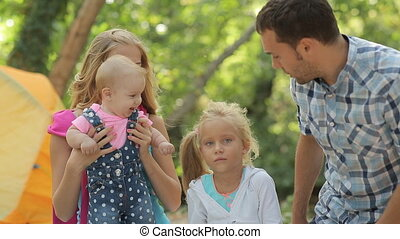 Beautiful family with two kids on a picnic, baby laughs and...