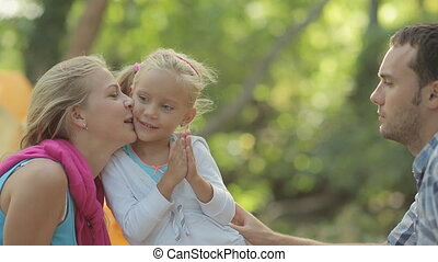 Funny little girl gives cheek for a kiss to her mother,...