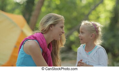 Incredibly fresh and happy mother and daughter playing and laughing at the picnic