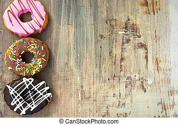 bright donuts on wooden background.