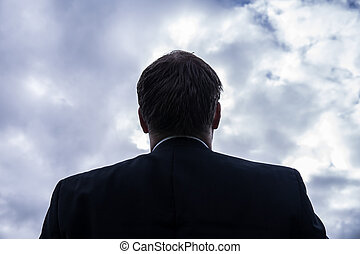 businessman lookin up to sky with stormy clouds