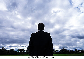 businessman and stormy clouds in landscape