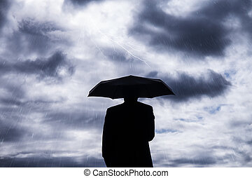 business man and umbrella in storm