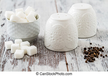 Pepper and Salt Shakers - Black peppercorns and sugar near...