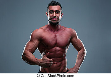 Happy muscular man showing thumb up