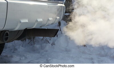 Exhaust gases from the muffler running car. Wheels of a car...
